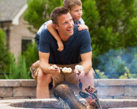 Father and son roast marshmallows over their Charlotte fire pit