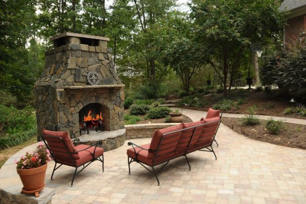 Natural stone patio design with a custom outdoor fireplace in Charlotte