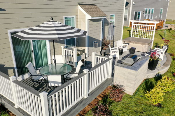 Outdoor space with a deck, outdoor grill, patio and surrounding landscaping