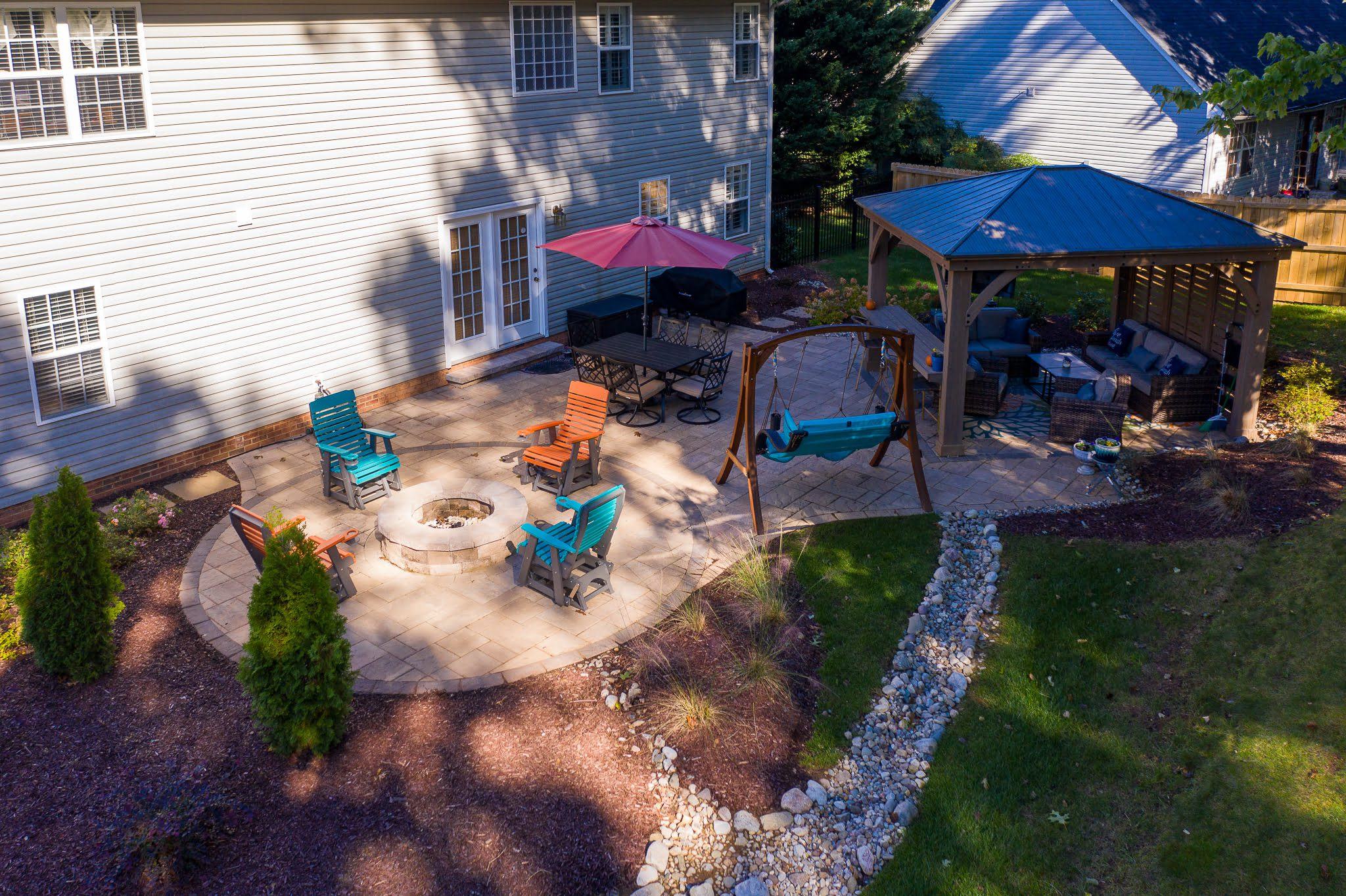 Custom patio with a fire pit and pergola, surrounded by landscaping in Monroe, NC