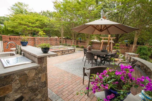 Brick and paver patio with an outdoor kitchen, garden and lawn furniture