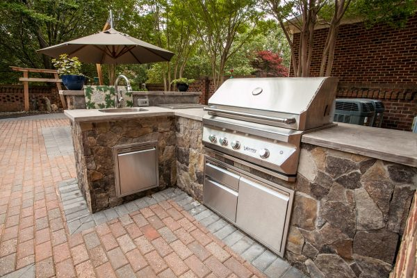 Stone outdoor kitchen above a brick patio built by MetroGreenscape