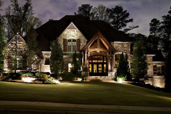 Outdoor lighting illuminating Charlotte home at dusk